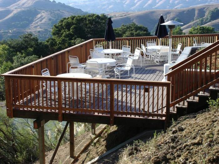 terrasse bois sur pilotis, parasols noirs, chaises blanches, tables rondes blanches, montagnes, rampe en bois