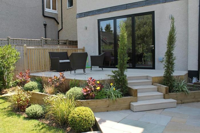 terrasse surélevée, plantes vertes, portes coulissantes noires, salon de jardin blanc et noir, façade beige