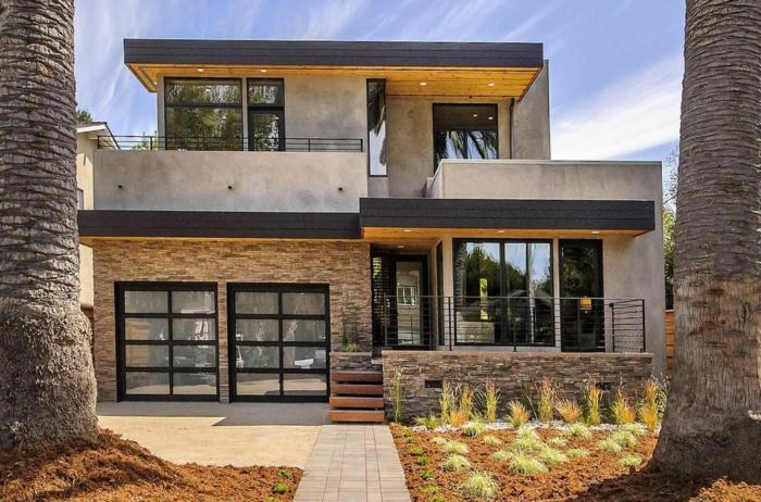 terrasse surélevée, façade en pierre, grandes fenêtres noires, éclairage led extérieur, rampe en fer forgé, arbres