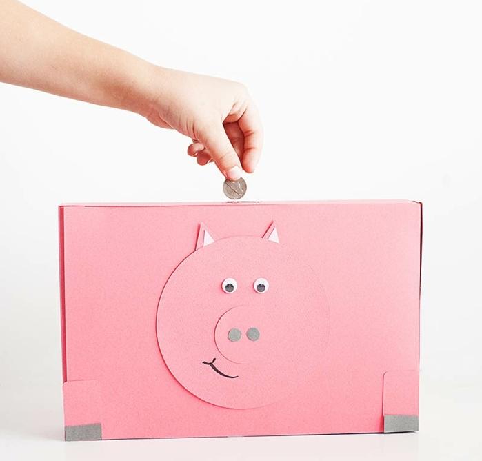 tirelire cochon couleur rose faite dans une boite a cereales, détails visage couleur rose, des yeux mobiles