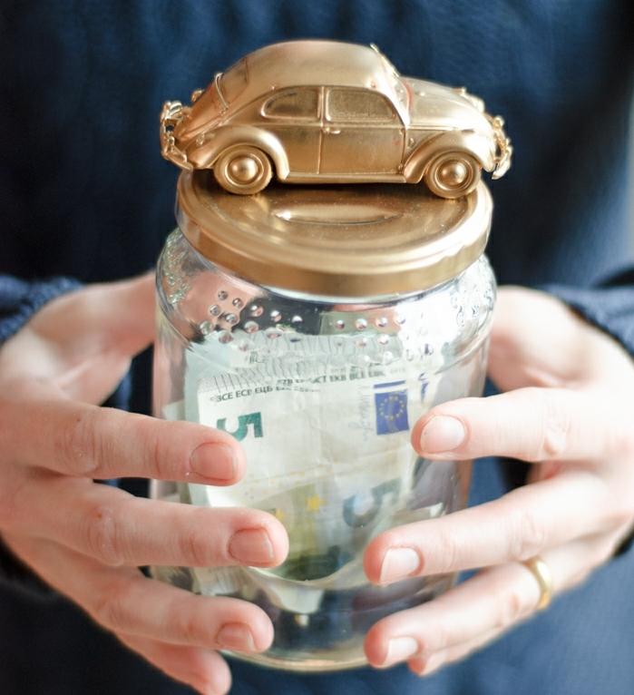 tirelire originale, économiser pour acheter une voiture, bocal en verre, billets de banque une figurine de voiture dorée dessus