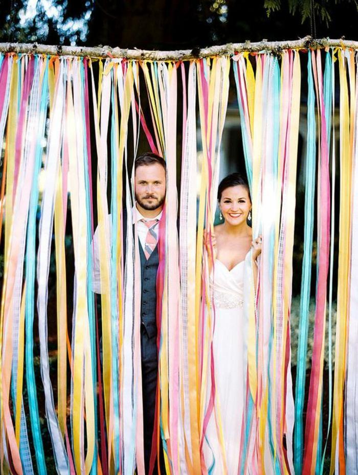 une branche décoré de guirlande à franges de tissu colorées, idée pour un cadre photobooth diy