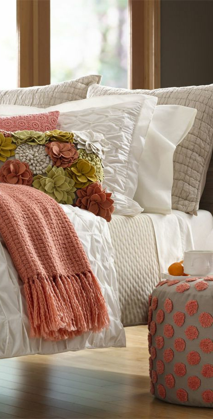 plaid de lit couleur abricot, tabouret gris à pois roses, coussins en rose corail et blanc