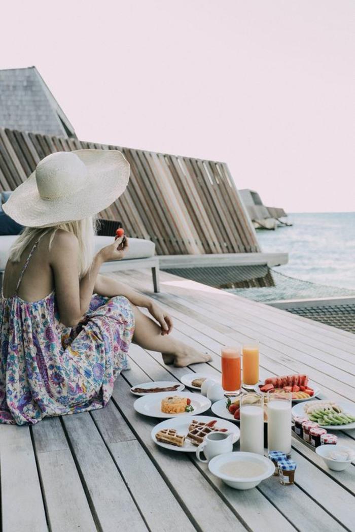 Déjeuner au bord de la mer - belle photo de femme qui mange son petit déjeuner habillée en robe imprimée fleurie bohème chic