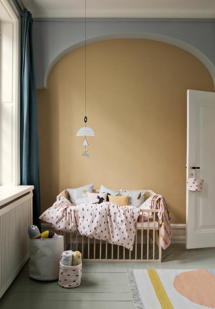 une chambre bébé de style scandinave au mur peint en couleur ocre et gris