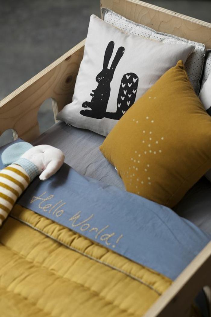 un berceau en bois naturel aux accents jaune ocre doré, couette et son oreiller assorti