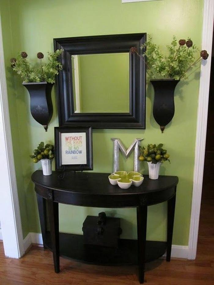 hall d'entrée maison en pistache et en blanc avec des vases noirs avec des fleurs