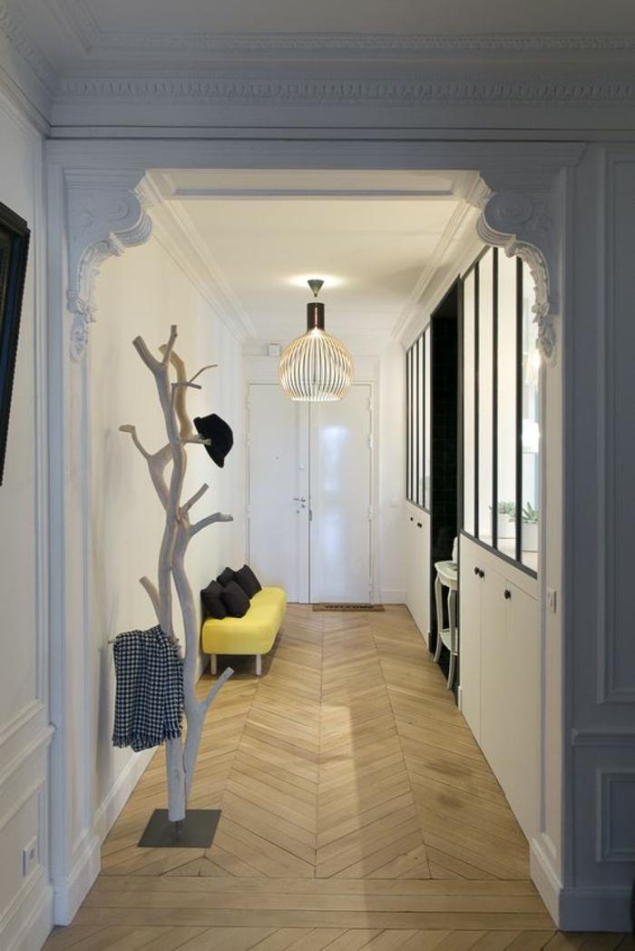 hall d'entrée maison avec porte-manteaux design arbuste blanc et petit meuble jaune contrastant avec le gris