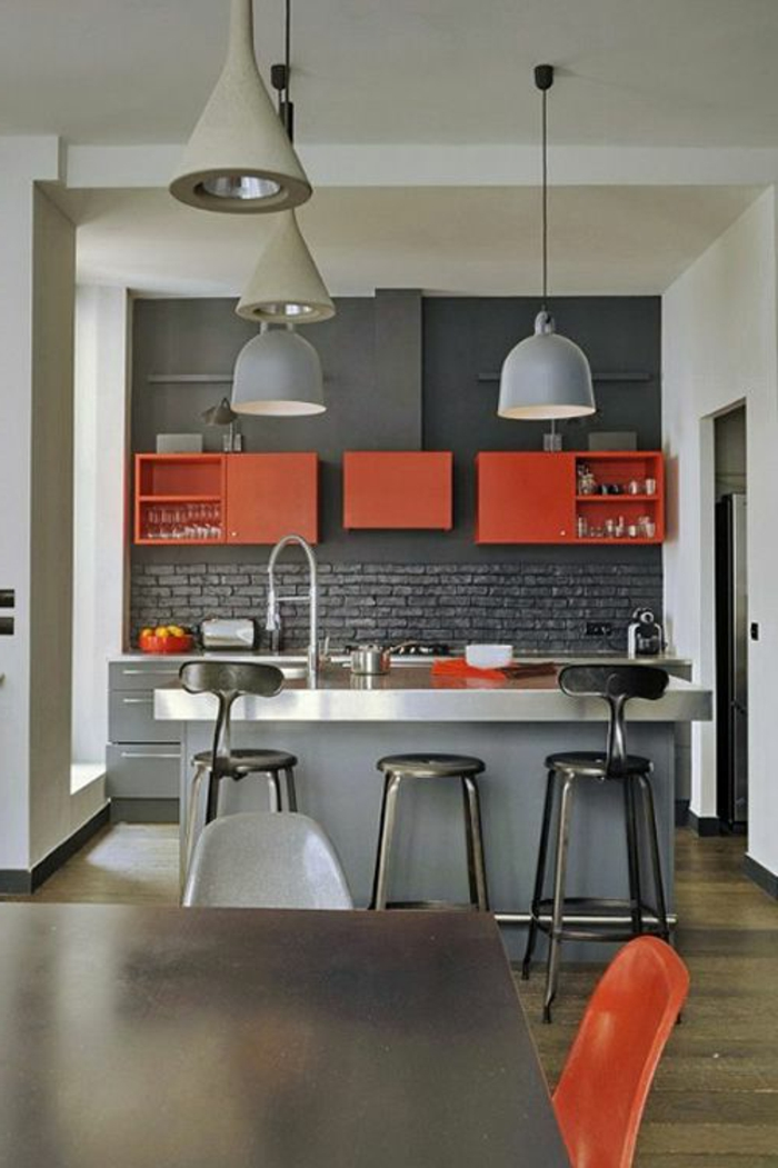 association de couleur avec le gris, untés suspendues oranges, mur en briques grises, lampes suspendues