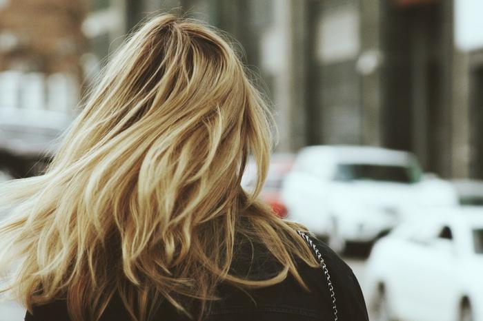 couleur blonde, sac à main avec chaîne métallique, veste noire, cheveux raids, blond californien
