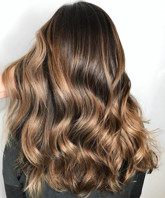 des cheveux bronde ondulés aux nuances chaudes de caramel et de miel