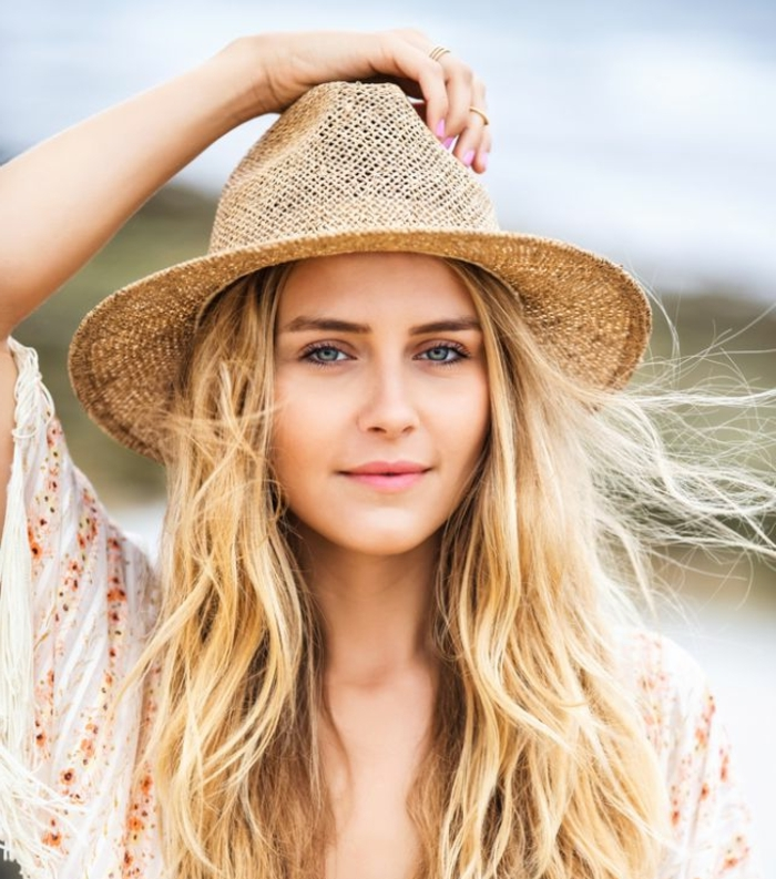 cheveux blond, boho style fille, chapeau en paille, manucure rose, chemise blanche, manches avec franges, blond californien