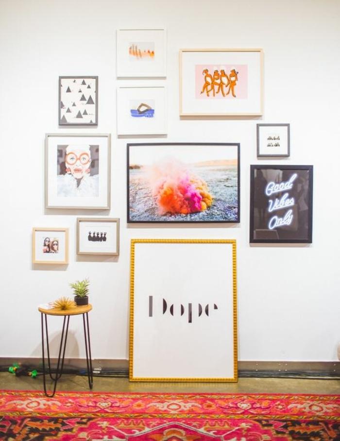 mur de cadres, tapis à motifs ethniques, petite table ronde en jaune, plantes, art print, photos