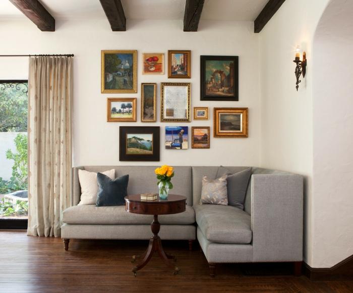 mur de cadres, grande fenêtre, vue sur le jardin, bougeoir, bouquet de fleurs jaunes, coussins décoratifs