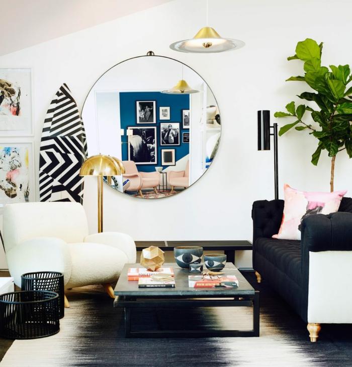 cadre rectangulaire, grand fauteuil, table basse, surf en blanc et noir, lampe dorée, lampe suspendue, canapé noir