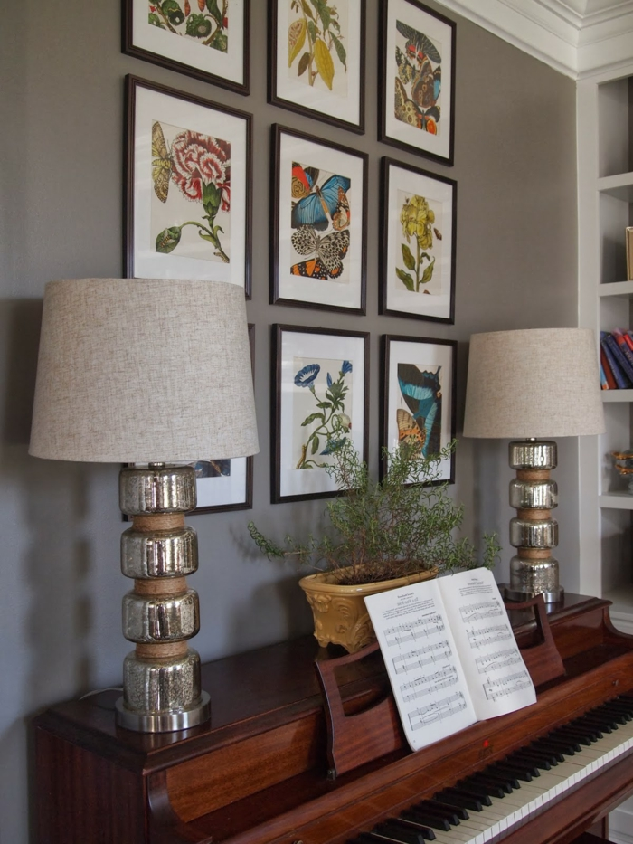 mur de cadres, piano massif, dessin papillon, bibliothèque en bois, murs taupe poudré, cahier de solfège