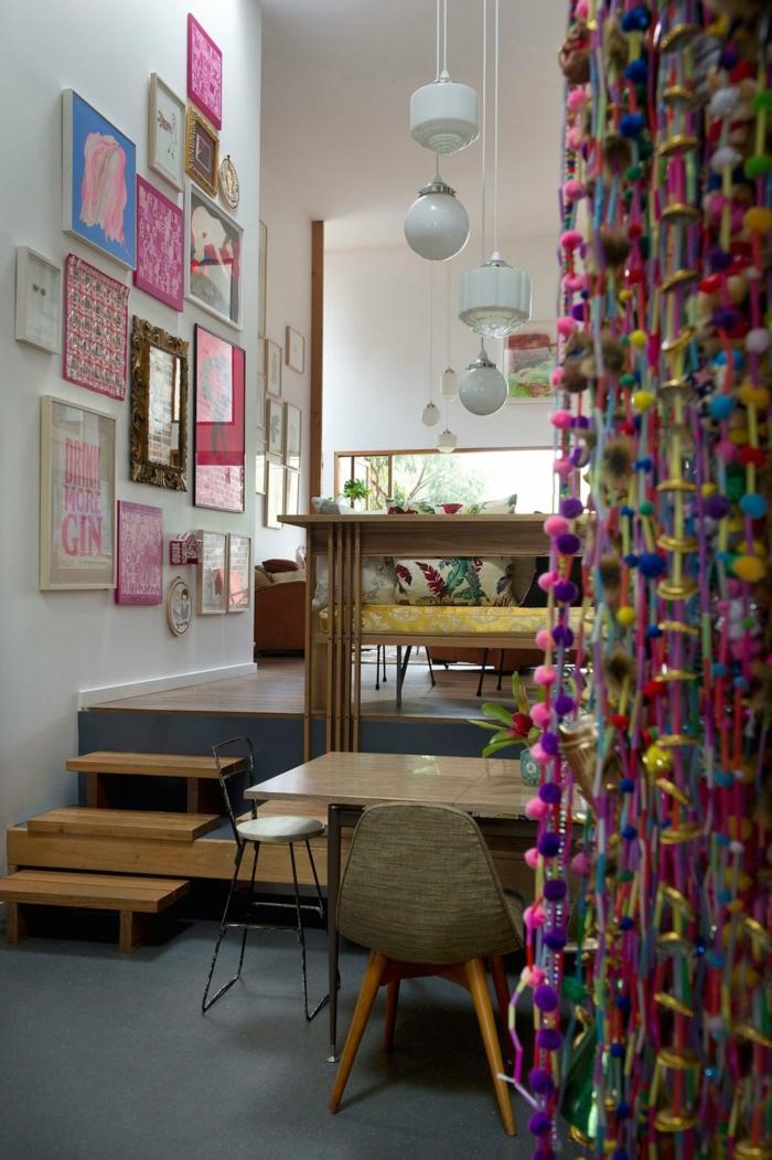 mur de cadres, plancher gris foncé, rideaux en pompons, lampes suspendues blanches, table en bois