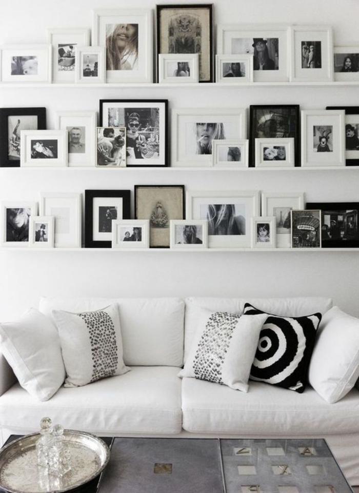 mur de cadres, salon blanc, coussins blancs, cadres photos, photos blancs et noirs