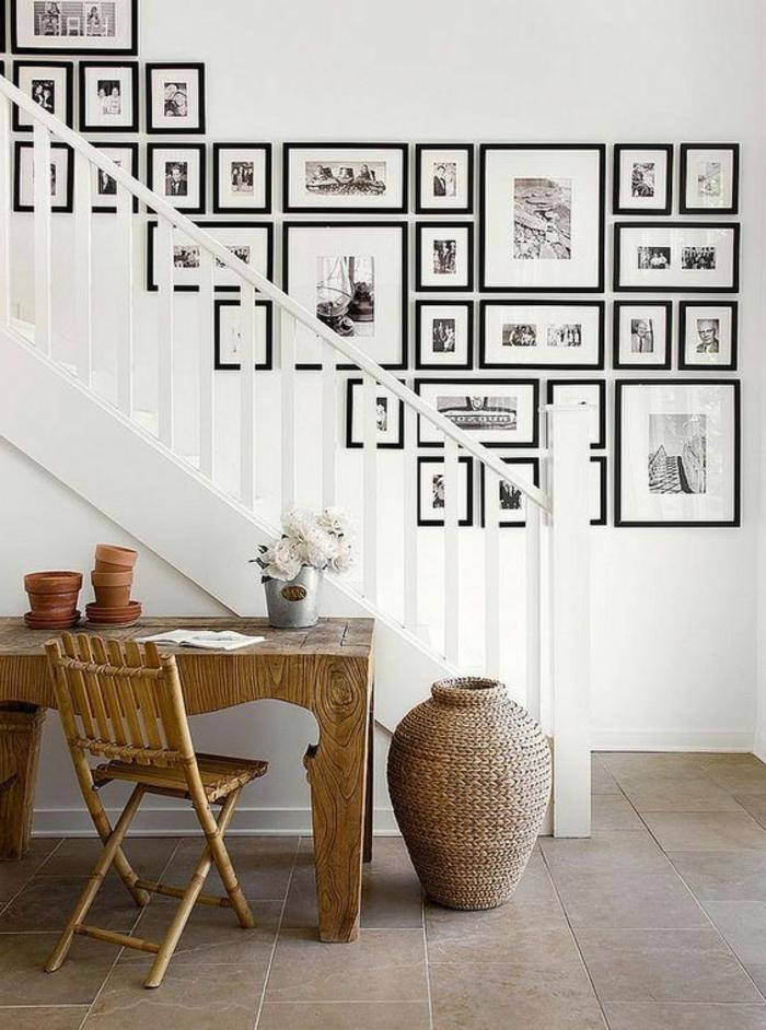 mur de cadres, table en bois, vase en rotin, carrelage beige, rampe en bois, murs blancs