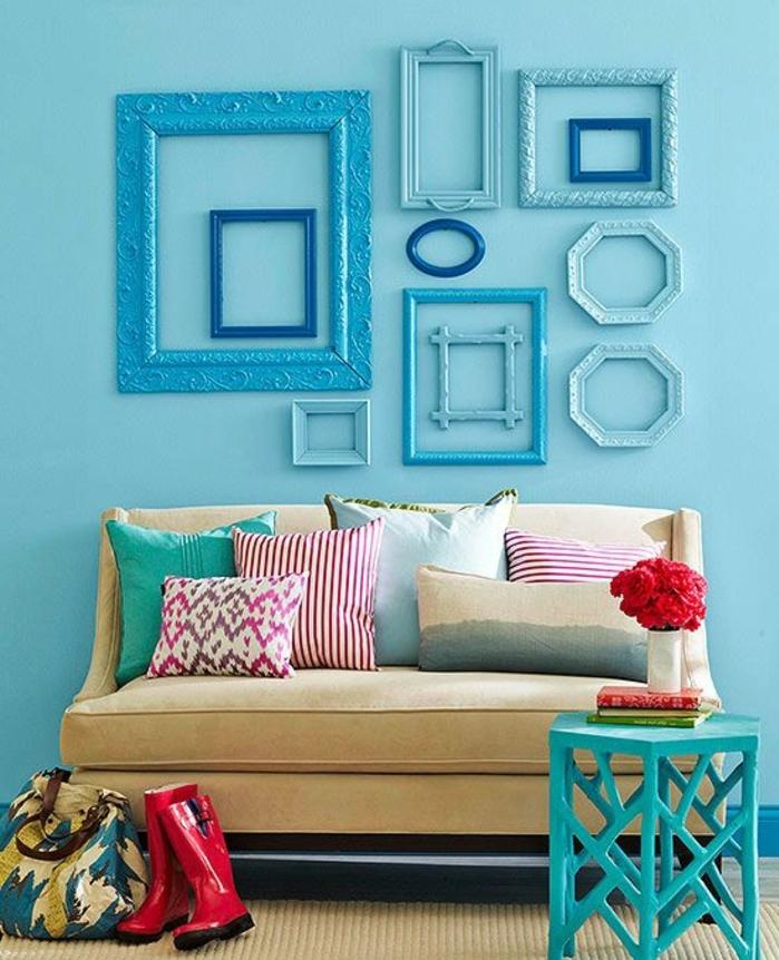 deco cadre vide avec plusieurs cadres bleus ovales et rectangulaires de tailles diverses, canapé couleur fauve, coussins multicolores, petite table de service bleue