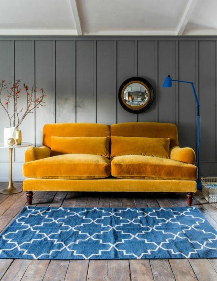 un canapé velours deux place couleur moutarde combiné ave un tapis graphique bleu