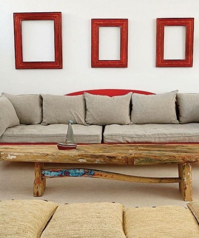 décorer un mur blanc de cadres rouges format divers, canapé gris et rouge, table en bois brut, coussins d assise par terre, tapis fauve