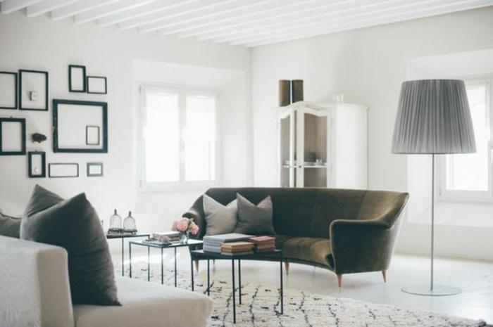 mur de cadres vides, canapé gris et canapé blanc, tapis blanc à motifs noirs, tables basse en metal, buffet vintage, revêtement sol et mur blancs