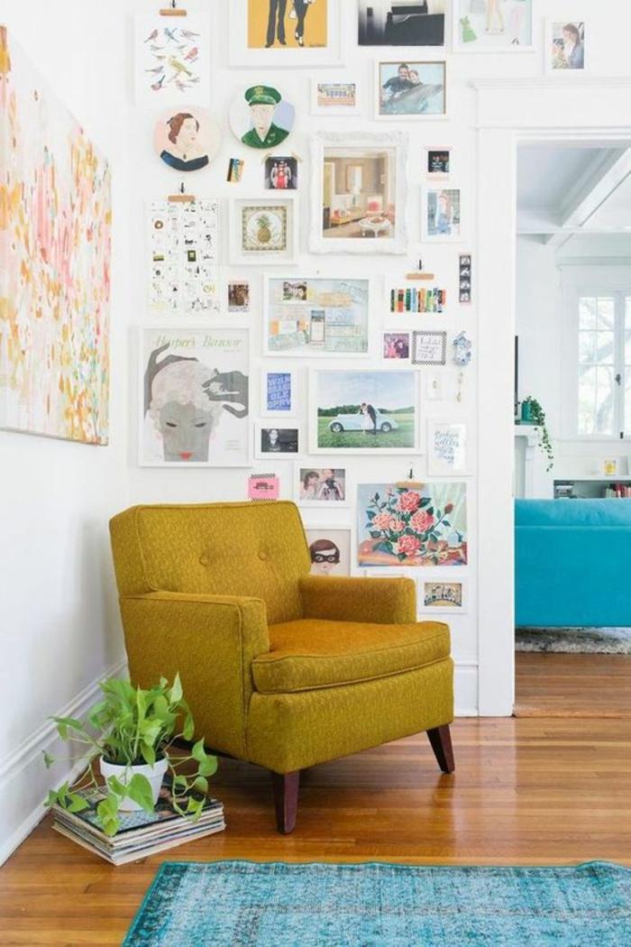 pan de mur en cadres pour un effet galerie d'art à la maison, canapé couleur jaune moutarde et tapis bleu turquoise vintage