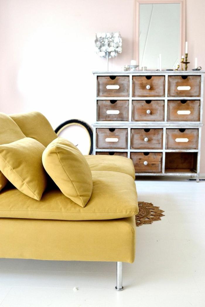un canapé ocre jaune au design contemporain qui s'associe à un mur rose pastel et à un plancher blanc