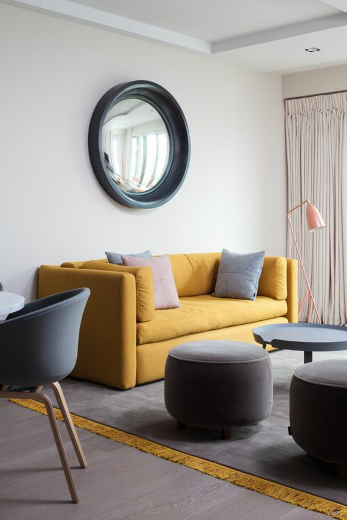 un salon gris et ocre jaune très épuré au mobilier scandinave, un grand miroir convexe original