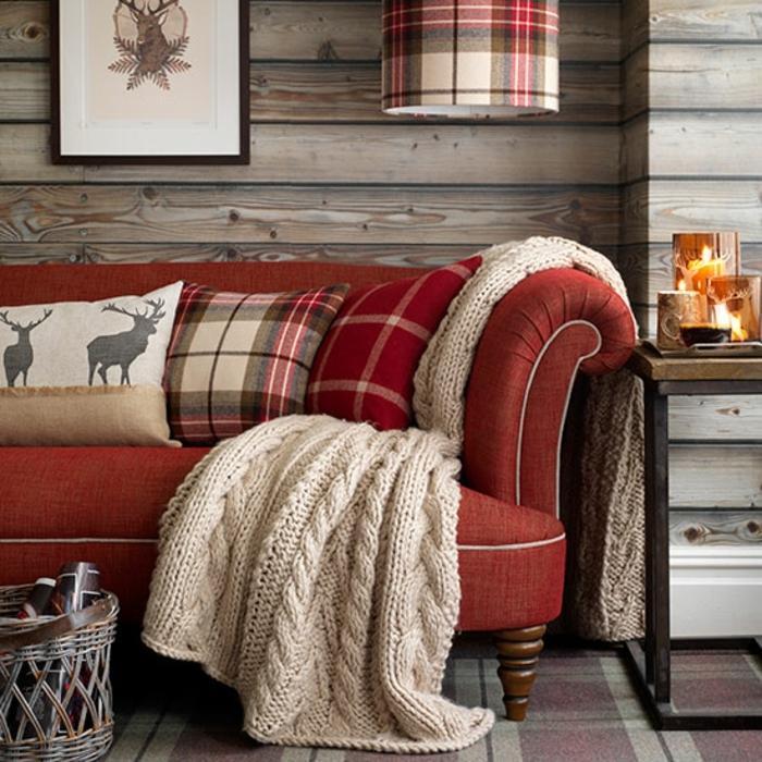 deco contemporaine rustique, canapé rouge, coussins multicolore, motifs cerf, deco murale dessin de cerf, tapis carrés, lambris en bois, plaid