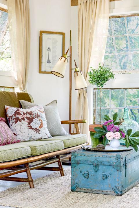 deco campagne chic, canapé vintage, coussins s assise vert pistache, table basse en coffre vintage bleu, bouquet de fleurs, lampe desig