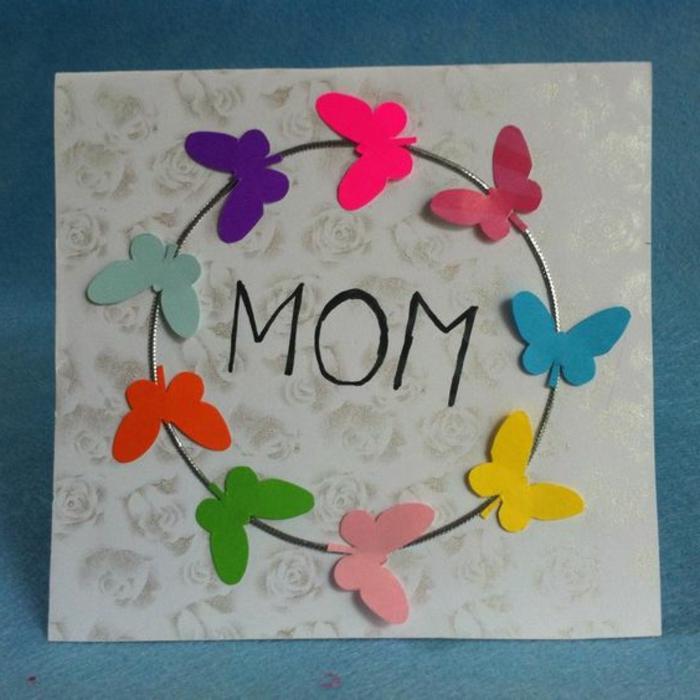 carte fête des mères à fabriquer, papillons qui volent en cercle collées sur un carré de papier à petits roses