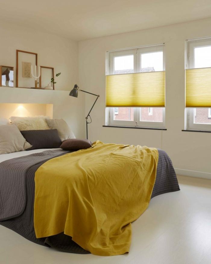 du linge de lit en gris et jaune ocre et des stores de la même couleur