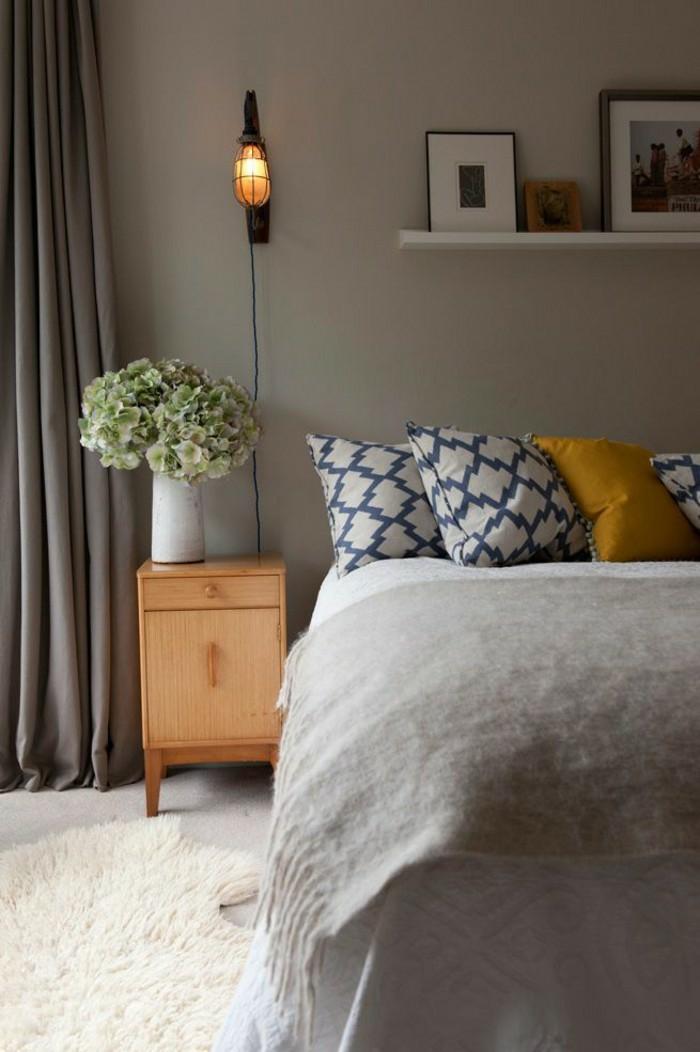 chambre à coucher élégante aux nuances du gris égayée par des coussins imprimés en ocre jaune et bleu