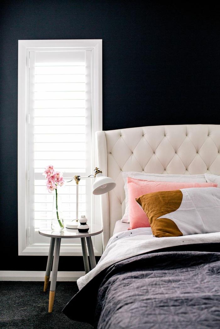 un linge de lit tendance en rose pastel et ocre jaune dans une chambre à coucher d'un chic sombre