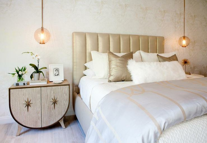 une suspension boule en verre rose doré de chaque côté du lit, une chambre à coucher aux accents dorés