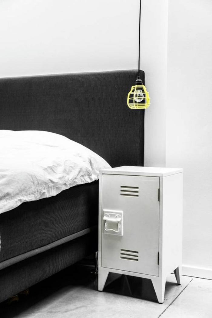 une lampe cage jaune à câble noir de style industriel, une table de chevet originale en métal façon casier d'école