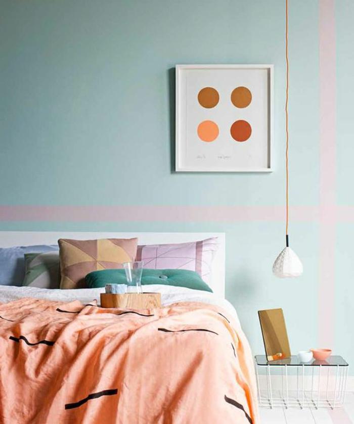 couverture couleur abricot, coussins déco géométriques, lampe blanche pendante, tableau abstrait et mur bleu