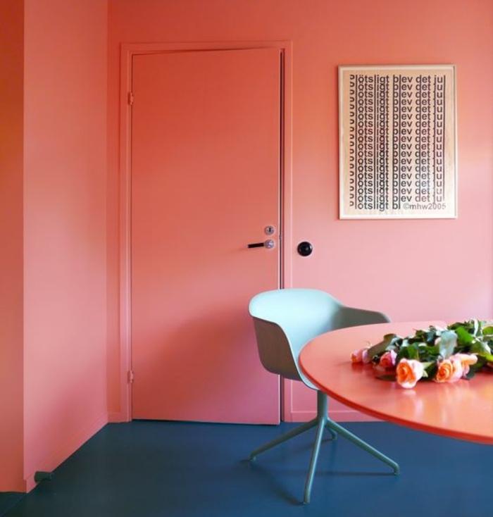 pièce couleur abricot, grande table corail, chaise couleur gris clair et sol peint bleu