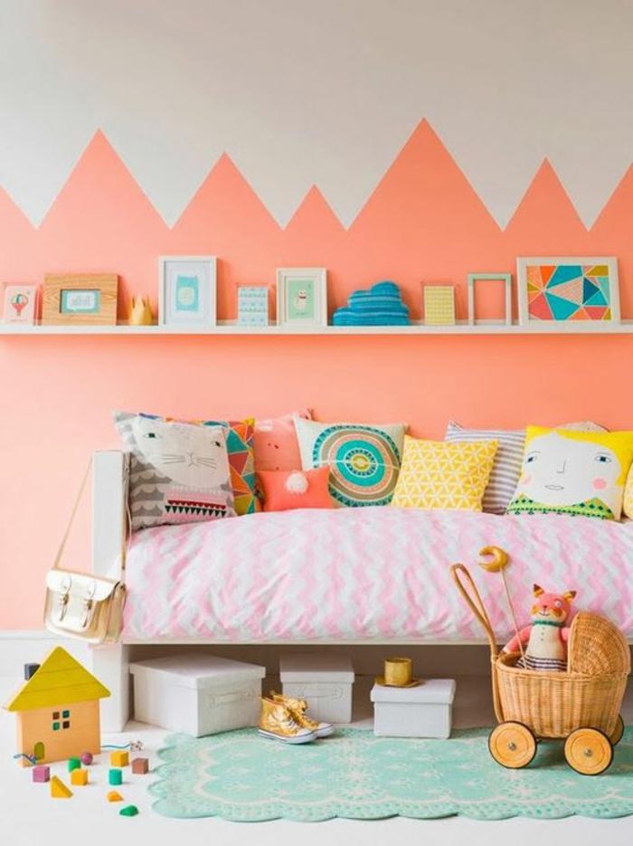 chambre d'enfant couleur abricot, étagère blanche, mur en corail et blanc, coussins déco en couleurs chaleureuses