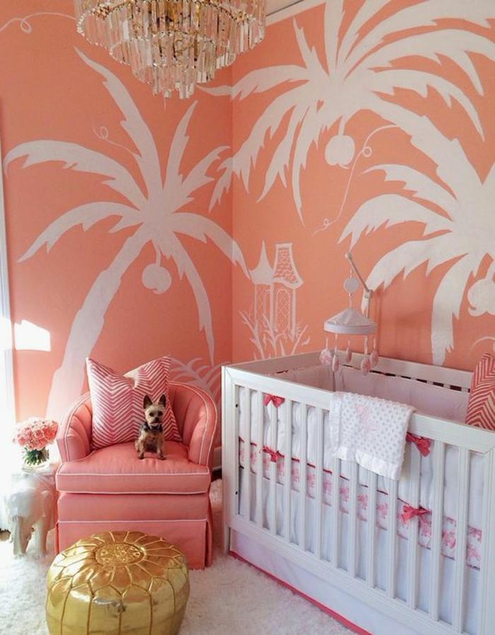 chambre d'enfant mur couleur saumon, palmiers blancs peints sur les murs, fauteuil rose et plafonnier en cristal
