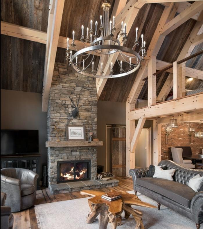 cheminee pierre dans un salon rustique, grande chandelier, table basse en bois design intéressant, tapis blanc cassé, canapé et fauteuils gris en cuir, maison ossature bois apparent