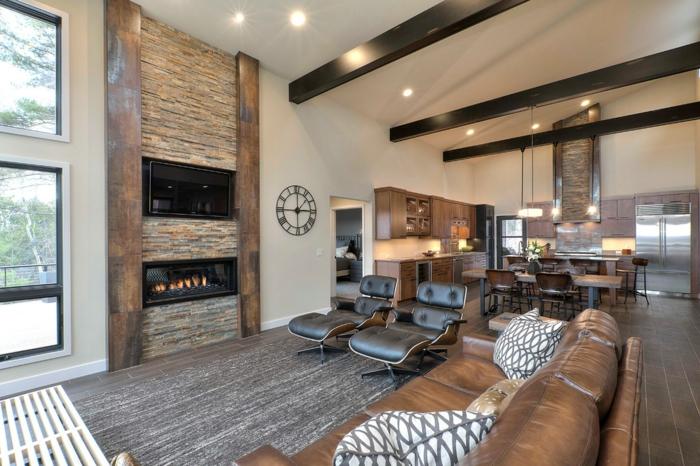 sol en pierre, cheminée moderne dans un mur en pierre, canapé et chaise longues en cuir, coussins en gris et blanc, horloge murale, cuisine et coin repas adjacent, espace ouvert