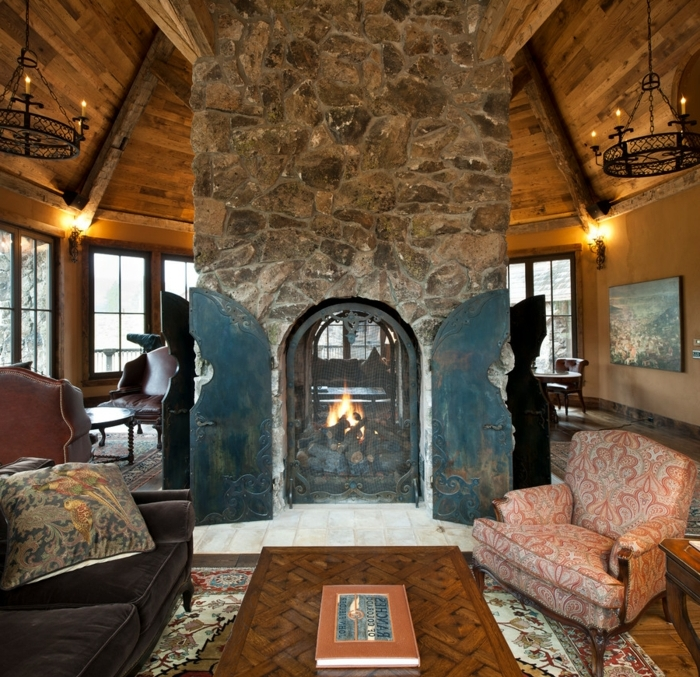 deco contemporaine et rustique, grands chandeliers noirs, cheminee pierre, maison ossature bois, table en bois, canapé vintage noir, et fauteuil retro, tapis oriental