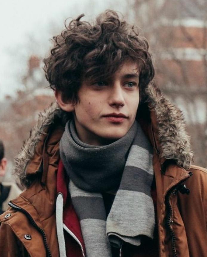 coiffure garcon avec des cheveux mi-long légèrement bouclés, effet coiffé décoiffé, look hiver, blouson marron, écharpe homme