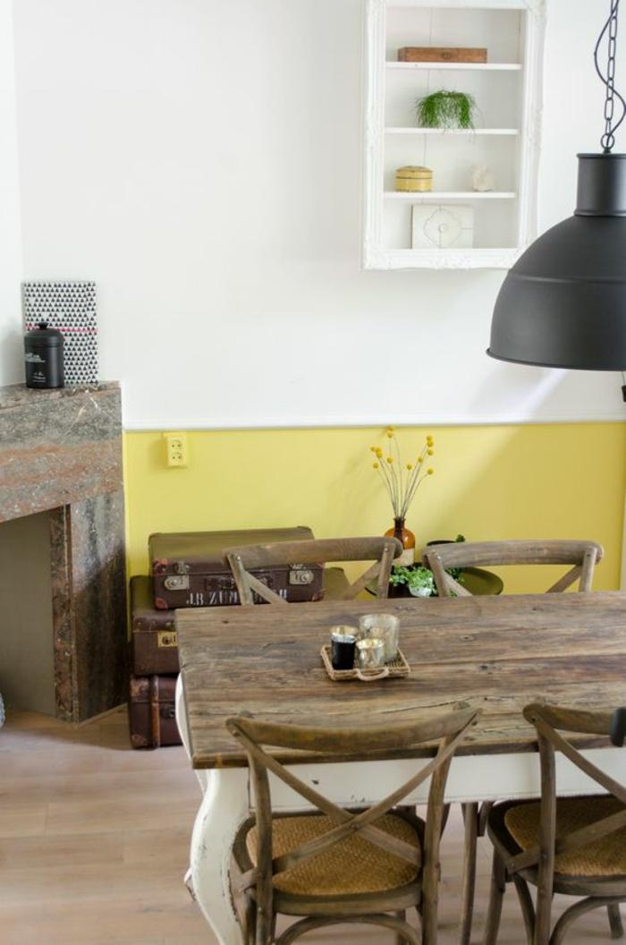 une salle à manger de style rustique au mur bicolore peint en ocre jaune et blanc, table de cuisine en bois brut