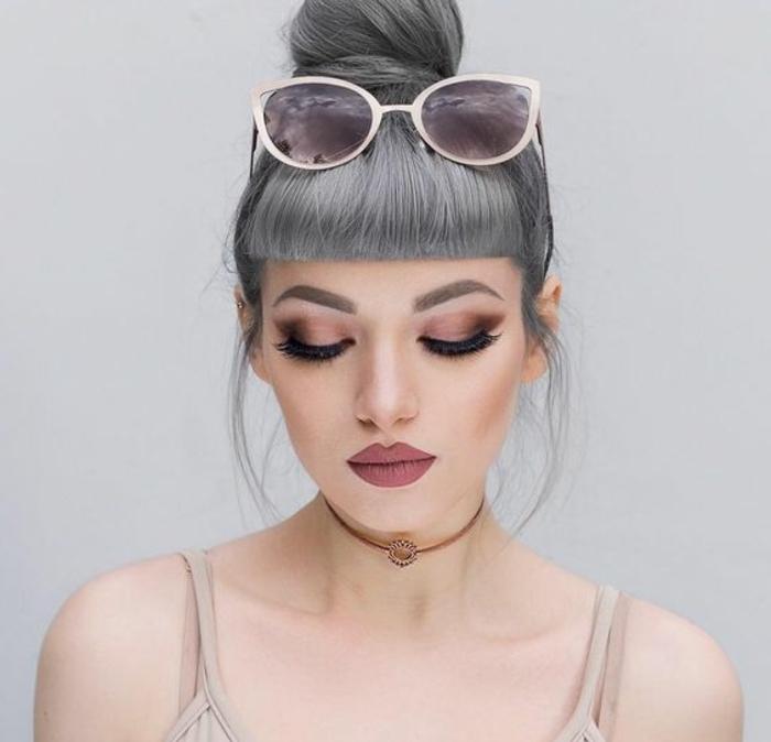 coloration grise, chocker marron, débardeur nude, décolleté en V, coiffure chignon gris avec frange