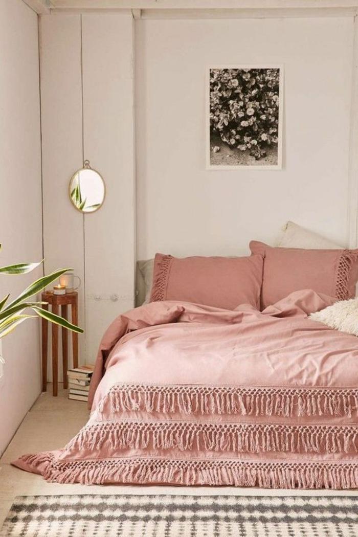 lit couleur abricot, petit chevet en bois, plante verte, photographie monochrome