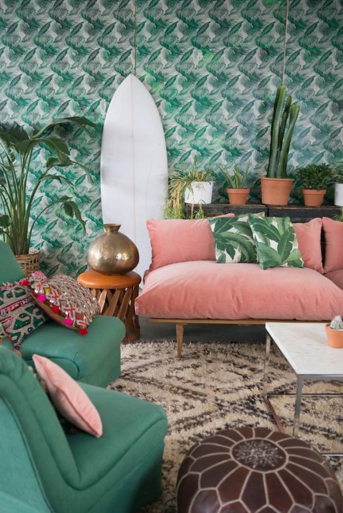 sofa couleur abricot, coussins tropicaux, papier peint végétal, planche de surf décorative